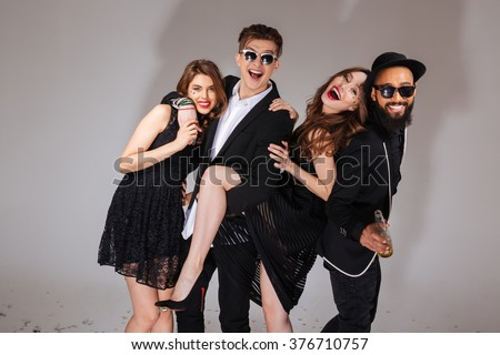 Multiethnic group of attractive joyful young friends hugging and having fun over white background - stock photo