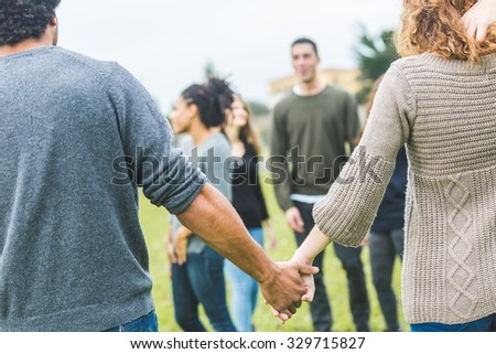 Multiethnic group of friends holding hands in a circle. The focus is on two hands with many other persons on background. Teamwork, integration, community, friendship concepts - stock photo
