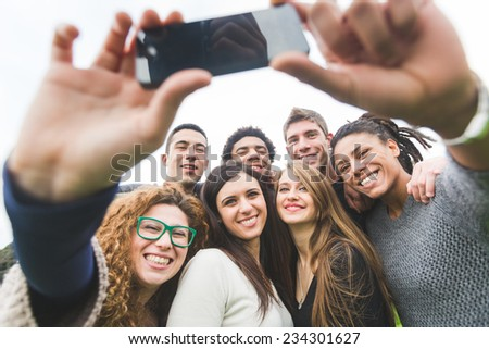 Multiethnic Group of Friends Taking Selfie at Park - stock photo