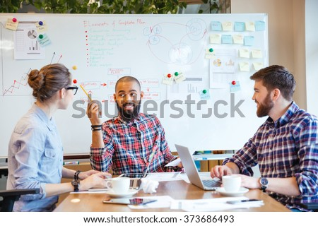 Multiethnic group of young people sitting in conference room and brainstorming on business meeting  - stock photo