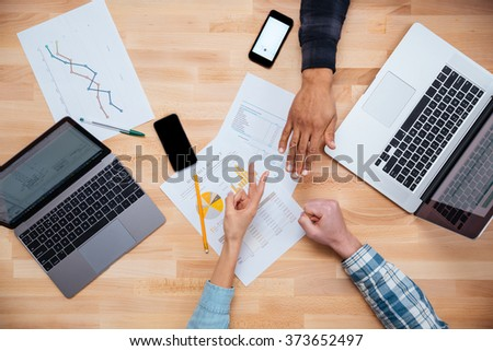 Multiethnic group of young people woking for monthly budget with laptops and gesturing rock paper scissors game  - stock photo