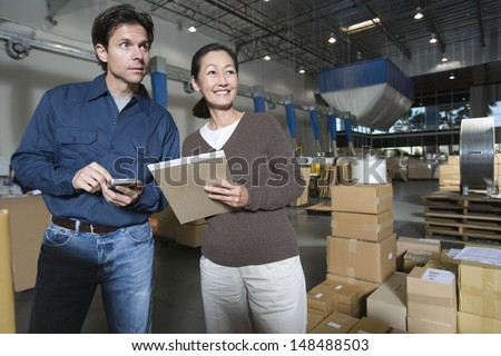 Multiethnic man and woman in distribution warehouse - stock photo