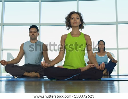 Multiethnic people sitting in lotus position at gym - stock photo