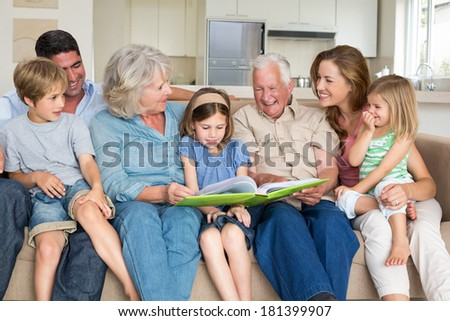 Multigeneration family reading storybook in living room - stock photo
