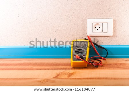 Multimeter and a socket on the wall in the room - stock photo