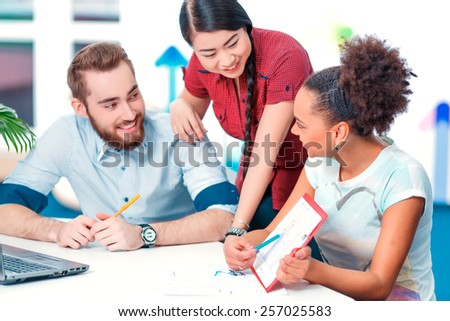 Multinational team. Young African and Chinese women and Caucasian man in smart casual looking at laptop together while working in creative space  - stock photo