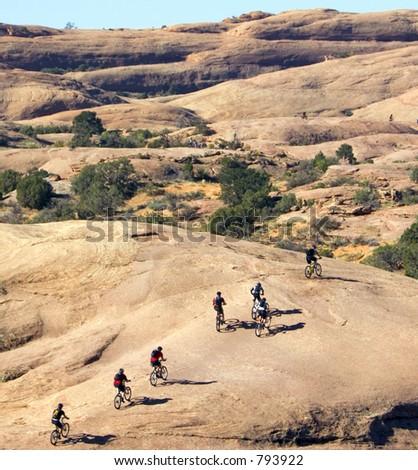 Multiple bike groups tackle the sheer rock in Moab, Utah - stock photo