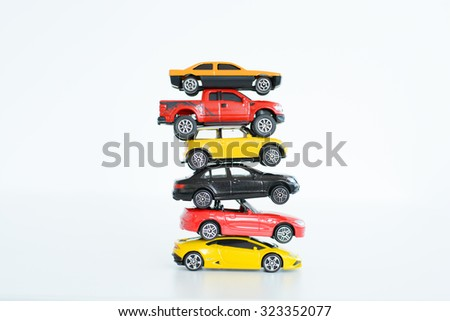 Multiple car toys on top of each other suggesting automotive industry problems - stock photo