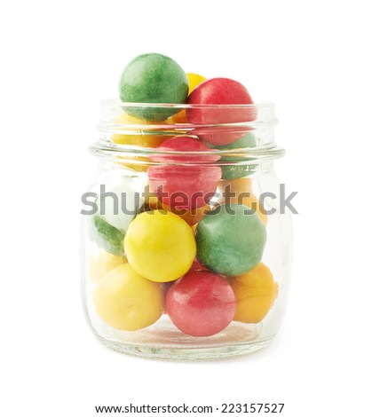 Multiple chewing gum balls in a glass jar isolated over the white background - stock photo