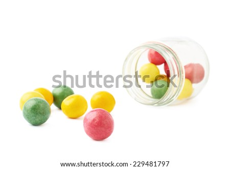 Multiple chewing gum balls next to a lying on its side glass jar, composition isolated over the white background - stock photo