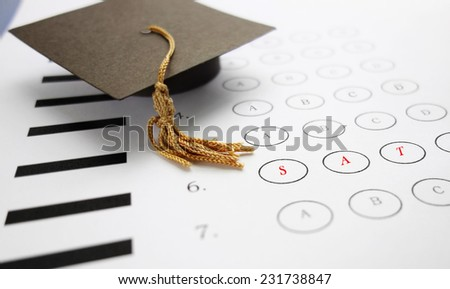 Multiple choice SAT exam with mini graduation cap                                - stock photo