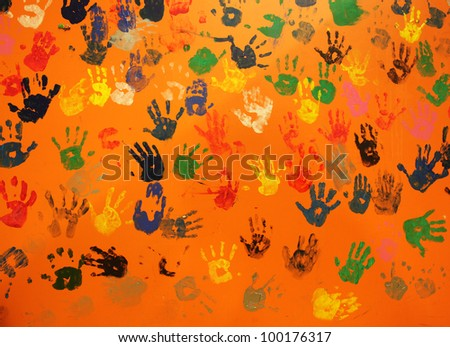 multiple colored hand prints on orange background - stock photo
