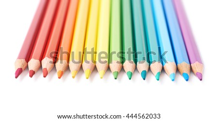 Multiple colorful color pencils composition arranged in a line to form a rainbow gradient, composition isolated over the white background, close-up crop fragment - stock photo