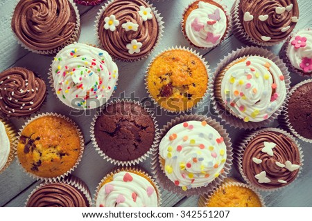 Multiple colorful nicely decorated muffins on a wooden background, top view - stock photo
