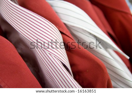 Multiple different shirts hanging. Close up, shallow dof. - stock photo