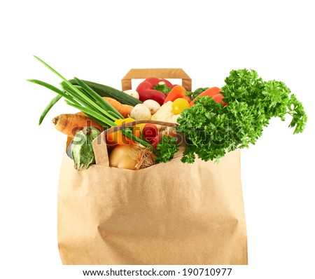 Multiple different vegetables in the paper bag isolated over the white background - stock photo