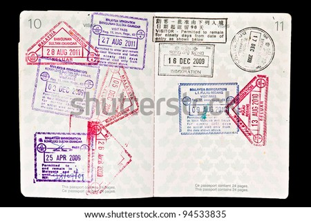 Multiple entries into Malaysia resulting in many entry and exit stamps in a Canadian passport. Isolated on black. Passport full and canceled with corner cut off. - stock photo
