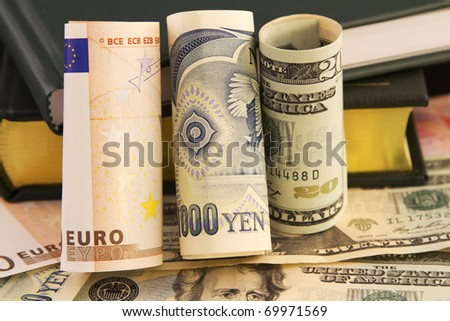 Multiple global currencies and books connect knowledge and data-driven, strategic global currency analysis to 21st century business - stock photo