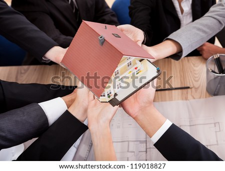 Multiple hands of diverse business people supporting a model house conceptual of partnership and teamwork - stock photo