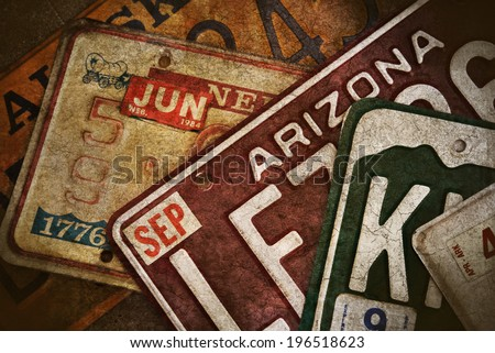 Multiple License Plates From Several United States. The color photo has a grunge texture applied to make it look old and worn. - stock photo