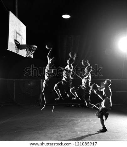 Multiple moves of a basketball player, jumping and throwing a basket at nighttime - stock photo