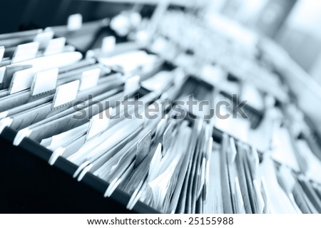 """Multiple rows of filing cabinets in an office or medical establishment, overflowing with files.  Narrow depth of field to emphasize the """"neverending"""" feeling - stock photo"""