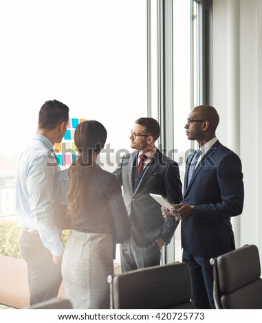 Multiracial business team having a meeting discussing their strategy and ideas for a new project as they stand in front of a bright office window - stock photo