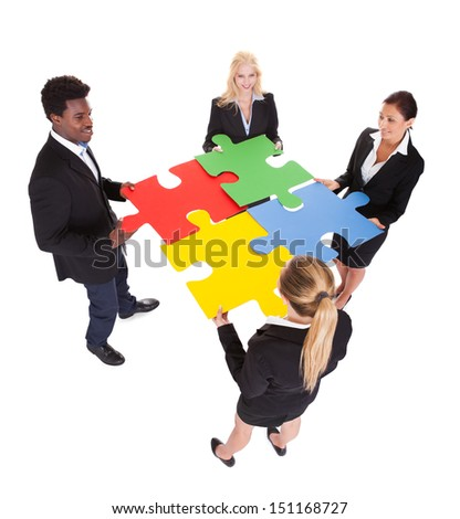 Multiracial Businesspeople Holding Jigsaw Puzzle Over White Background - stock photo