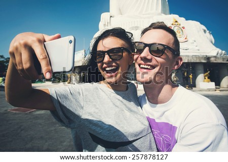 Multiracial couple of students in love smile and make selfie photo with smartphone camera while traveling across Asia on vacation - stock photo