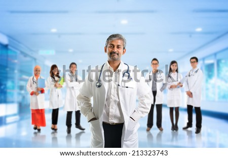 Multiracial diversity Asian medical team, expertise senior and mature doctors leading young practitioners, standing inside hospital. - stock photo