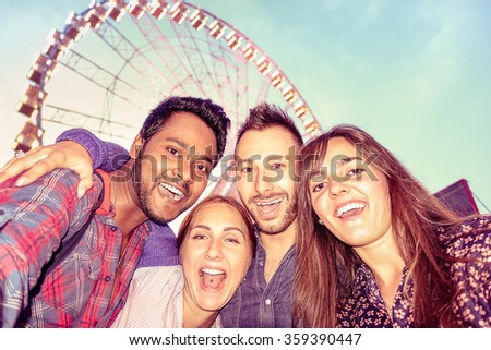 Multiracial group of best friends taking selfie at ferris wheel -Two couples of happy young american students having fun with mobile phone - Modern concept of  friendship and cultural integration - stock photo