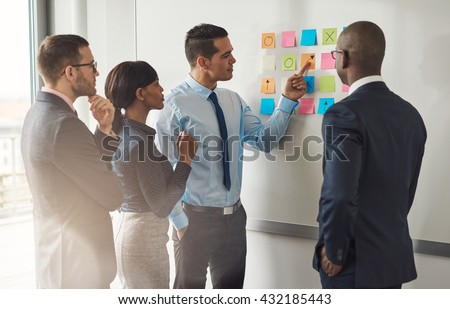Multiracial group of colleagues discussing a business plan standing around a set of colorful memo notes stuck on the wall - stock photo