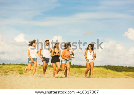 Multiracial group of friends running on the beach. There are four girls and three boys, wearing trunks and colourful t-shirts. Friendship and lifestyle concepts. Yellow filter added. - stock photo