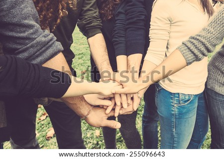 Multiracial group of friends with hands in stack, strong concept about teamwork and cooperation, also refers to immigration and friendship. - stock photo