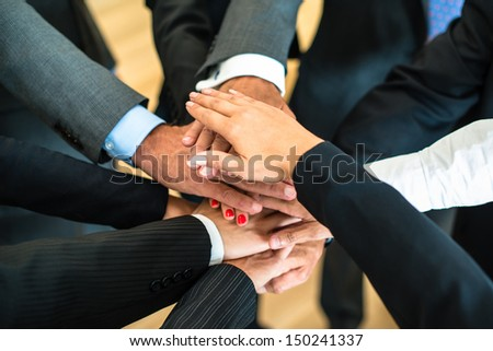 Multiracial group of nine diverse businesspeople standing in a circle facing each other joining hands in a team - stock photo