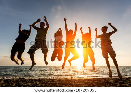 Multiracial Group of People Jumping at Beach, Backlight - stock photo