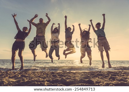 Multiracial group of people jumping at beach. Backlight shot. Happiness, success, friendship and community concepts. - stock photo