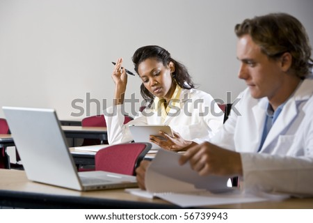 Multiracial medical students wearing lab coats studying in classroom - stock photo
