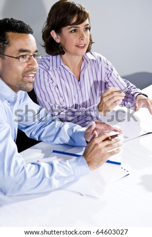 Multiracial office workers in boardroom meeting watching presentation, taking notes, focus on woman - stock photo