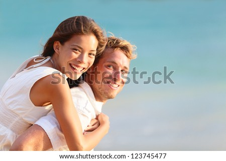 Multiracial people: Happy couple piggybacking cheerful on beach during summer holidays vacation. - stock photo