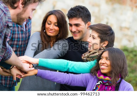 Multiracial Students with Hands on Stack - stock photo