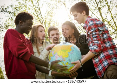 Multiracial Teen Couple Holding Globe Map - stock - stock photo