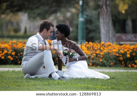 Multiracial wedding couple posing on the grass in the park - stock photo