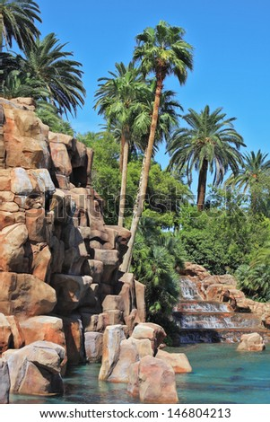 Multistage stone fountain surrounded by tropical vegetation and palm trees. The spectacular cascade fountain.  - stock photo