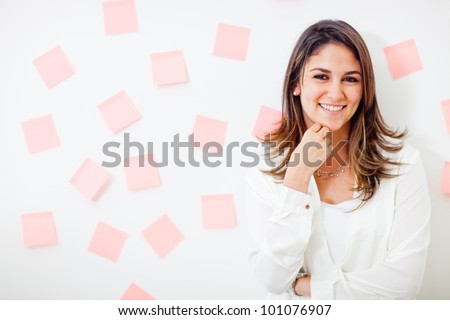 Multitask businesswoman with post-its and smiling - stock photo