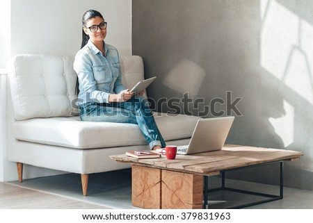 Multitasking. Beautiful young woman in glasses looking at camera with smile and working with touchpad while sitting on the couch in office - stock photo