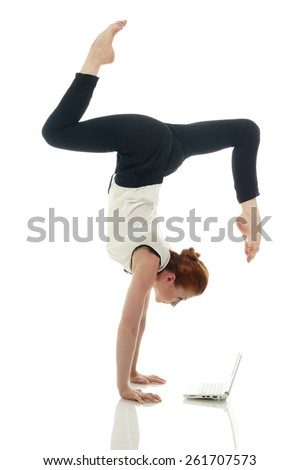 Multitasking. Girl doing handstand with laptop - stock photo