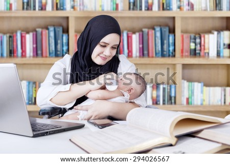 Multitasking young mother nursing her baby with milk from bottle while working in the library - stock photo