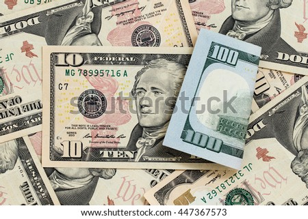 Multitude of banknotes, nominal value of ten dollars at  front side and nominal value of hundred dollars at reverse side. Concept of potential profitable investments and successful business. Close-up - stock photo