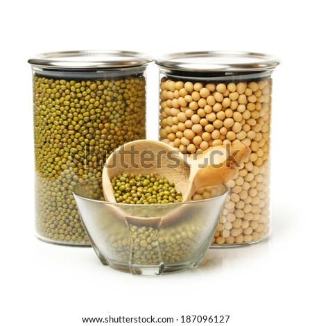 multitude of green Azuchi beans (Vigna radiata) and gold soybean on white background - stock photo
